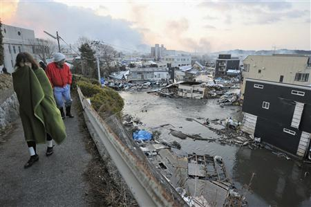 Houses swept by a tsunami are seen as residents walk in Kesen Numa, Miyagi prefecture March 12, 2011. The biggest earthquake on record to hit Japan rocked its northeast coast on Friday, triggering a 10-metre tsunami that killed hundreds of people and swept away everything in its path. REUTERS/Kyodo
