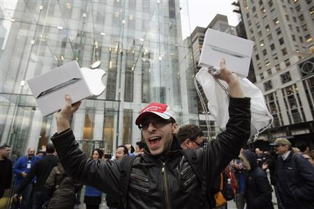 A customer holds up a pair of Apple's iPad 2 tablet after purchasing the second generation device at the Apple's flagship 5th Avenue store in New York March 11, 2011. REUTERS/Lucas Jackson