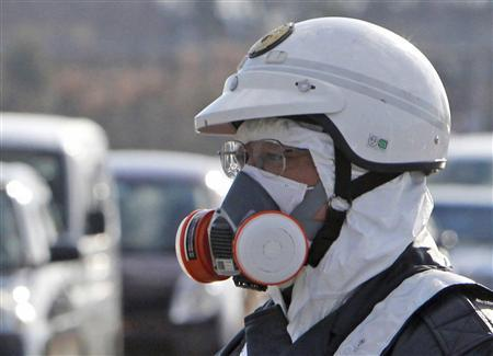 A police officer wearing a respirator guides people to evacuate away from the Fukushima Daiichi nuclear plant following an evacuation order for residents who live in within a 10 km (6.3 miles) radius from the plant after an explosion in Tomioka Town in Fukushima Prefecture March 12, 2011. REUTERS/Asahi Shimbun