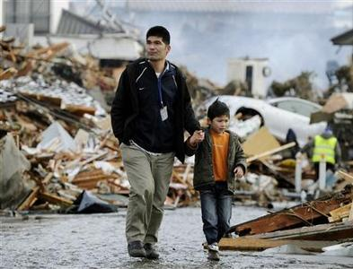 A man and boy walk between houses destroyed by a tsunami and earthquake in Sendai, northeastern Japan March 12, 2011. REUTERS/Kyodo