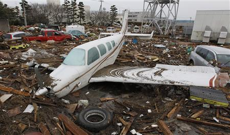 Wreckages of cars and an airplane are seen at a devastated area after an earthquake and tsunami near Sendai airport in northern Japan, March 13, 2011. REUTERS/Jo Yong-Hak