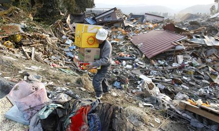 A man salvages possessions from the rubble in Rikuzentakata, northern Japan after the magnitude 8.9 earthquake and tsunami struck the area, March 13, 2011. REUTERS/Lee Jae-Won