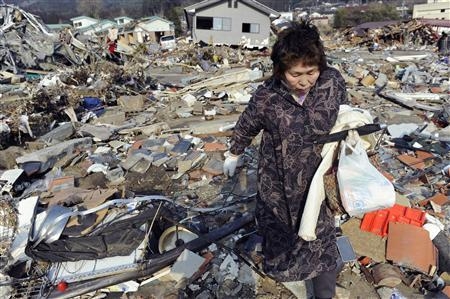 A woman searches for supplies amid piles of debris in Ofunato City, Iwate Prefecture in northern Japan, March 13, 2011. REUTERS/Kyodo