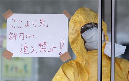 A technician in protective gear looks out of a window next to a sign reading ''No entry except for those with permission'' at a makeshift facility to screen, cleanse and isolate people with high radiation levels in Nihonmatsu, northern Japan March 14, 2011, after a massive earthquake and tsunami that are feared to have killed more than 10,000 people. REUTERS/Yuriko Nakao