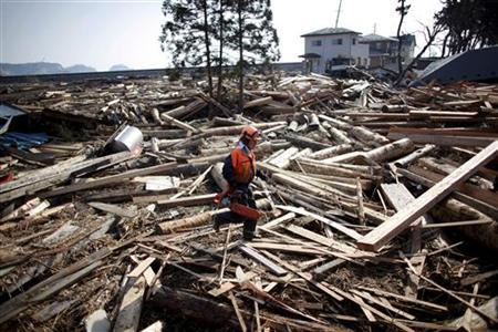 An emergency worker walks amidst debris in an area hit by an earthquake and tsunami in Kuji, Iwate prefecture March 14, 2011. REUTERS/Aly Song