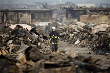 A Japanese rescue worker walks through a destroyed residential area of tsunami-hit Otsuchi March 14, 2011. REUTERS/Damir Sagolj