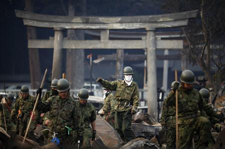 Japanese rescue workers search through rubble in front of a Shinto shrine in residential area of tsunami hit Otsuchi March 14, 2011. REUTERS/Damir Sagolj