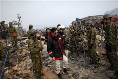 President of the International Federation of Red Cross and Red Crescent Tadateru Konoe (C) walks among rescue workers searching through rubble in a residential area of tsunami-hit Otsuchi March 14, 2011. ''After my long career in the Red Cross where I have seen many disasters and catastrophes, this is the worst I have ever seen. Otsuchi reminds me of Osaka and Tokyo after the Second World War when everything was destroyed and flattened,'' Tadateru Konoe told Reuters during a visit to the coastal town. In the town of Otsuchi in Iwate prefecture, 12,000 out of a population of 15,000 have disappeared following Friday's massive earthquake and tsunami. REUTERS/Damir Sagolj