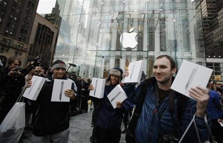 Customers hold up their Apple's iPad 2 tablets after purchasing the second generation devices at the Apple's flagship 5th Avenue store in New York March 11, 2011. REUTERS/Lucas Jackson