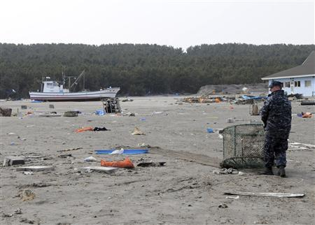 A U.S. Navy sailor assigned to the Naval Air Facility Misawa hauls debris during a cleanup effort March 14, 2011 at the Misawa Fishing Port, Japan. REUTERS/Mass Communication Specialist 2nd Class Devon Dow-US NAVY/Handout