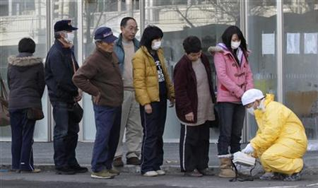 People queue to be screened by a technician in protective gear for signs of possible radiation in Nihonmatsu, northern Japan, March 14, 2011, after a massive earthquake and tsunami that are feared to have killed more than 10,000 people. REUTERS/Yuriko Nakao