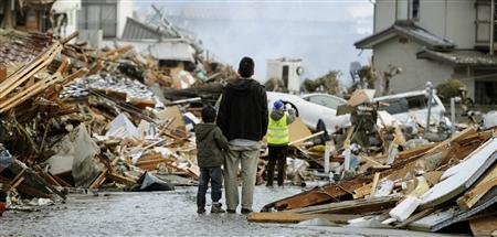 A man and child look out over destroyed homes after a tsunami and earthquake in Sendai, northeastern Japan March 12, 2011. REUTERS/Kyodo