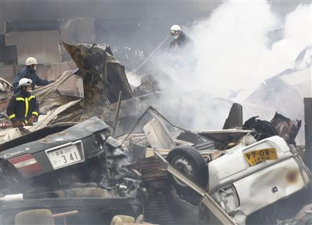 Firemen put out fire at a devastated area hit by earthquake and tsunami in Kesennuma, Miyagi Prefecture in northern Japan, March 15, 2011. REUTERS/Kim Kyung-Hoon