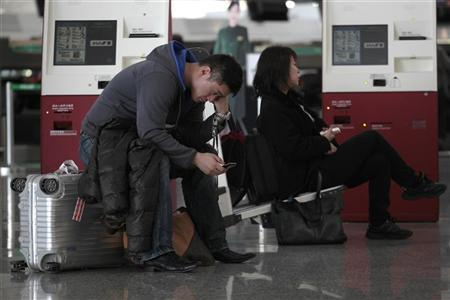 Japanese travellers rest near the ANA ticket counter after all the flights to Tokyo were cancelled after a tsunami and earthquake hit Japan on Friday, at Hong Kong international airport March 12, 2011. REUTERS/Tyrone Siu
