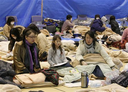 Evacuees sit through an earthquake at a temporary shelter at a stadium in Koriyama, northeastern Japan March 12, 2011. REUTERS/Jo Yong-Hak