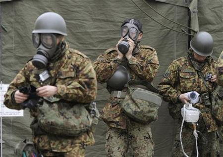 Japan Self-Defense Force officers prepare for a clean-up at a radiation affected area in Nihonmatsu, Fukushima Prefecture in northern Japan, March 15, 2011. REUTERS/Kyodo