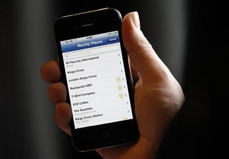 A journalist uses the new Facebook Deals application on a mobile phone at its official launch in London, January 31, 2011. REUTERS/Suzanne Plunkett