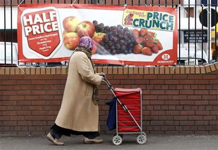 A woman walks past a shop advertisement in south London January 26, 2011. REUTERS/Suzanne Plunkett