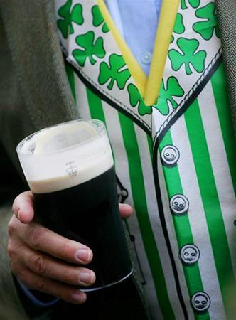 A racegoer holds a pint of Guinness on St Patrick's Day on the third day of the Cheltenham National Hunt Festival on March 17, 2005. REUTERS/Mike Finn-Kelcey