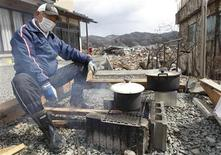 <p>A man cooks at his home at a devastated area hit by the earthquake and tsunami in Kesennuma, north Japan, March 17, 2011. REUTERS/Kim Kyung-Hoon</p>