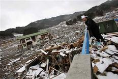 <p>A survivor looks on at the debris from the second floor of his destroyed house in Yamada, Iwate Prefecture, days after the area was devastated by a magnitude 9.0 earthquake and tsunami, March 17, 2011. REUTERS/Aly Song</p>