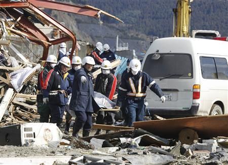 Police officers and rescue workers carry the body of a victim at a village destroyed by an earthquake and tsunami a week ago in Ofunato, Iwate Prefecture, northeast Japan March 18, 2011. REUTERS/Lee Jae-Won