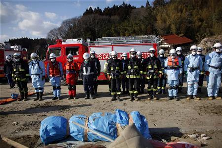 Emergency workers bow in front of a body they retrieved from the debris in Rikuzentakata, Iwate prefecture, where the earthquake and tsunami hit last week, March 18, 2011. REUTERS/Aly Song