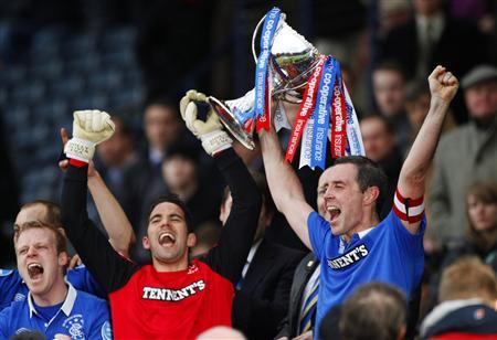 Rangers' team captain David Weir (R) holds aloft the winners trophy after their CIS Cup final soccer match victory over Celtic at Hampden Park stadium in Glasgow, Scotland March 20, 2011. REUTERS/David Moir