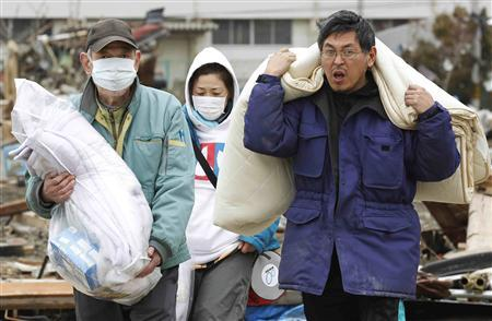 Evacuees carry their belongings, which they found in their houses, at an area destroyed by earthquake and tsunami, in Ishinomaki, north Japan March 21, 2011. REUTERS/Kim Kyung-Hoon