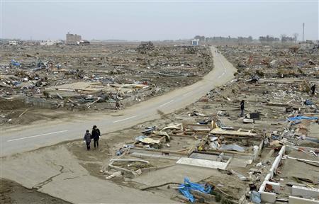 People walk amidst debris of buildings wrecked by last week's earthquake and tsunami in Natori City, Miyagi Prefecture, northeastern Japan, March 20, 2011. REUTERS/Yegor Trubnikov