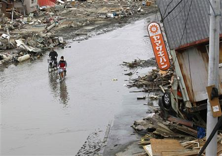 People ride their bicycles in a flooded road at an area destroyed by an earthquake and tsunami, in Ishinomaki, north Japan, March 21, 2011. REUTERS/Kim Kyung-Hoon
