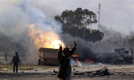A rebel fighter gestures in front of burning vehicles belonging to forces loyal to Libyan leader Muammar Gaddafi after an air strike by coalition forces along a road between Benghazi and Ajdabiyah March 20, 2011. REUTERS/Goran Tomasevic