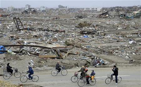 People ride bicycles amidst debris of buildings wrecked by last week's earthquake and tsunami in Natori City, Miyagi Prefecture, northeastern Japan, March 20, 2011. REUTERS/Yegor Trubnikov