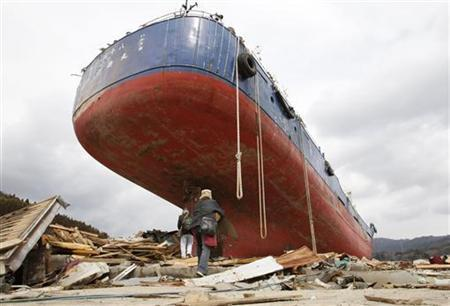 Takeshi Yokoyama, 70, and his wife Umeko, 64, carry boxes of food given as relief for tsunami victims in front of a ship washed on to land at destroyed residential area of Kesennuma, Miyagi Prefecture, nearly two weeks after the area was devastated by a magnitude 9.0 earthquake and tsunami, March 22, 2011. REUTERS/Issei Kato