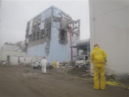 Efforts to spray water into the No. 4 reactor at the Fukushima Daiichi Nuclear Power Plant, which was struck by an earthquake and tsunami in Tomioka, Fukushima Prefecture, northeastern Japan, are seen in this March 22, 2011 handout photograph released by Tokyo Electric Power Co. . Picture taken March 22, 2011. REUTERS/Tokyo Electric Power Co./Handout