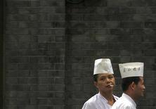 <p>Шеф-повар курит перед входом в ресторан в центре Пекина 7 сентября 2010 года. Китай запретит курение в общественных местах, находящихся в закрытых помещениях, в мае, пытаясь оградить население от пагубной привычки в стране с крупнейшими в мире объемами производства сигарет, сообщило министерство здравоохранения. REUTERS/David Gray</p>
