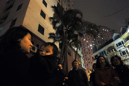 Residents stand outside a building after an earthquake, in Hanoi, March 24, 2011. REUTERS/Kham