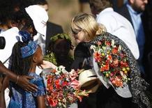 <p>Madonna touches the chin of a girl who gives her flowers as she arrives to lay the foundation of a multi-million dollar girls' school she is building in Chinkota, outside Lilongewe in Malawi in this October 26, 2009 file photo. A charitable group backed by Madonna has scrapped its plan to build the school in Malawi due to mismanagement, the New York Times reported on Thursday. REUTERS/Siphiwe Sibeko</p>