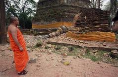 <p>Буддийский монах смотрит на поврежденную в результате землетрясения пагоду, 25 марта 2011 года. Как минимум 63 человека погибли в результате сильного землетрясения в Мьянме в четверг, сообщили государственные СМИ. REUTERS/Chaiwat Subprasom</p>