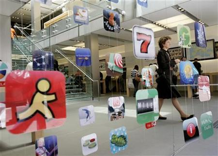 A woman walks past icons for Apple applications at the company's retail store in San Francisco, California April 22, 2009. REUTERS/Robert Galbraith
