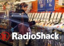 <p>Foto de archivo de una mujer revisando teléfonos móviles al interior de una tienda de Radio Shack en Cambridge, EEUU, abr 28 2008. Las tiendas deben responder a la llamada para hacer más fácil y atractiva la compra a través de los teléfonos móviles o se arriesgan a quedar desconectadas de la mayoría de los usuarios, dijo Arc Worldwide, la división de servicios de márketing de la agencia de publicidad Leo Burnett. REUTERS/Brian Snyder</p>