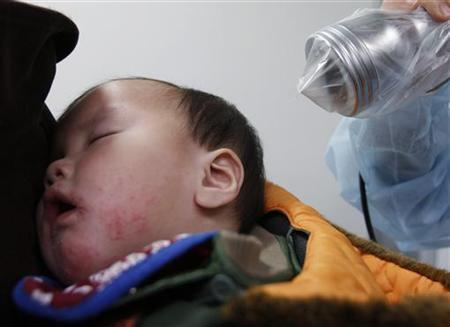 Tsubasa Nishi, a nine-month-old baby from Minamisoma in Fukushima, undergoes a screening test for signs of nuclear radiation by a doctor as he sleeps on his 27-year-old mother Azusa's back at a health center in Yonezawa, northern Japan, 98 km (61 miles) from the Fukushima nuclear plant, March 25, 2011. REUTERS/Issei Kato