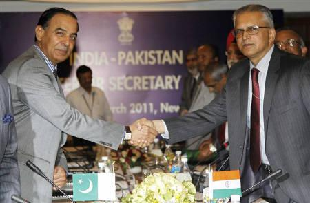 India's home secretary G. K. Pillai (R) shakes hands with his Pakistani counterpart Chaudhary Qamar Zaman before the start of the Indo-Pak secretary level talks in New Delhi March 28, 2011. REUTERS/B Mathur