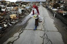 <p>A victim covers her face as she cries while carrying relief supplies more than two weeks after the area was devastated by a magnitude 9.0 earthquake and tsunami, through a destroyed area of Yamada town, Iwate Prefecture in northern Japan March 26, 2011. REUTERS/Damir Sagolj</p>