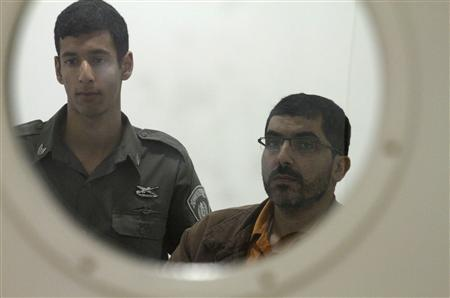 Gazan engineer Dirar Abu Sisi (R) is seen through a door window as an Israeli prison guard stands next to him at the district court in Petah Tikva, near Tel Aviv, March 27, 2011. REUTERS/Stringer