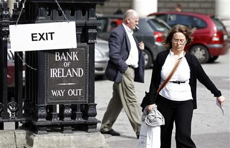 People walk past a bank in Dublin March 31, 2011. Ireland will publish what is meant to be the final bill for propping up its banks on Thursday in a last-ditch bid to convince investors it can avoid deepening Europe's debt woes with a damaging restructuring. REUTERS/Cathal McNaughton