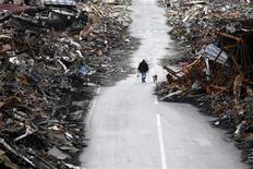 <p>Мужчина гуляет с собакой в разрушенном городе Кесеннума 22 марта 2011 года. Сотрудники береговой охраны спасли в пятницу собаку, унесенную три недели назад в открытое море в результате землетрясения и цунами в Японии. REUTERS/Issei Kato</p>
