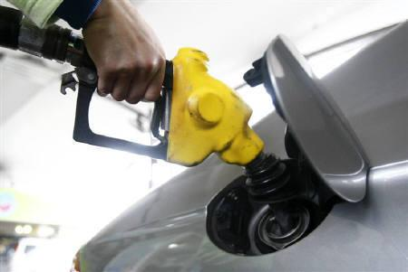 An attendant tops up petrol for a vehicle at a gas station in Taipei March 1, 2011. REUTERS/Pichi Chuang/Files