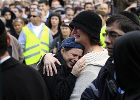 Mourners cry during the funeral of Ehud Fogel, 36, his wife Ruth, 35, and their children 11-year-old Yoav, 4-year-old Elad, and 3-month-old Hadas in Jerusalem, March 13, 2011. REUTERS/Baz Ratner