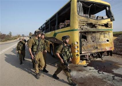 Israeli soldiers walk past a bus that was damaged by an anti-tank missile fired from the Gaza Strip into southern Israel on the road between kibbutz Nahal Oz and kibbutz Sa'ad April 7, 2011. . REUTERS/Baz Ratner